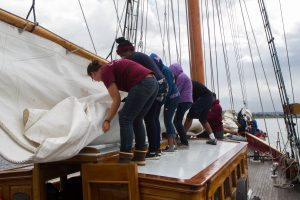 Crew members and Pathfinders help roll the sails as the boat prepares to return to port.