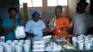 Adventist volunteers prepare to serve supper for residents of Petite Savanne one of the most affected by Tropical Storm Erika which hit the Caribbean Island of Dominica on Aug. 17, 2015. ADRA and the Roseau Community Services have been providing three meals every day to about 120 people since the shelters were opened in Dominica. Credit: ANN/ADRA Dominica.