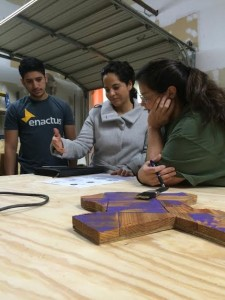 Ana Patterson (Enactus faculty sponsor), Gabriel Castillo (Enactus Student VP for Projects), and Stella (COI wood shop manager) discuss logo options for Beeyond Designs. Photo by Darcy Force, used by permission.
