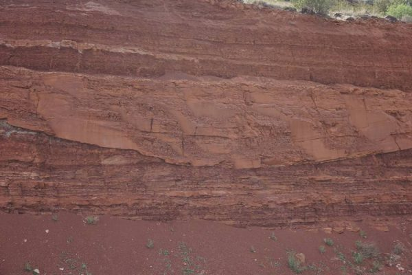 Figure 8. Filled-in flood channel in the Kayenta Formation preserved between horizontal deposition layers (St. George, UT). The ash layer shown in Figure 7 is visible to the center left of this photograph, with the flood stream having cut through it.